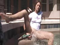 Maria playing with a hose in the pool
