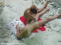 Naked couple caught unaware on a rocky beach