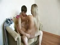 Teen couple having sex in a love seat