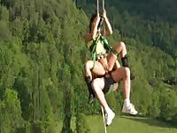 Mountainclimbing couple having sex hanging on a rope