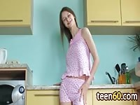 Horny teen playing with her toy in the kitchen