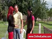 Two dressed ladies sharing a dick outdoors