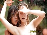 Two lovely girls getting wet outdoors